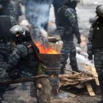 Rohamrendőrök pihennek a kormányellenes tüntetők egyik barikádjánál Kijevben 2014. január 28-án. (MTI/EPA/Makszim Sipenkov)
