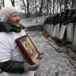 Szentképpel a kezében áll egy asszony a kormányellenes tüntetők sorfala előtt Kijevben 2014. január 28-án. (MTI/EPA/Zurab Kurcikidze)