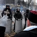Feszülettel a kezében áll egy pap a kormányellenes tüntetők sorfala előtt Kijevben 2014. január 28-án. (MTI/EPA/Zurab Kurcikidze)