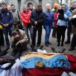 Kormányellenes tüntetők a rohamrendőrökkel vívott összecsapások közben elesett társaik véres ukrán zászlóval letakart holtteste mellett, a kijevi Függetlenség terén 2014. február 20-án. MTI Fotó: Beliczay László