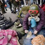 Egy azonosított halott nevét írja a lábára egy kormányellenes tüntető a tetem elszállítása előtt a rohamrendőrökkel vívott összecsapások közben a Függetlenség terén Kijevben, 2014. február 20-án. MTI Fotó: Beliczay László