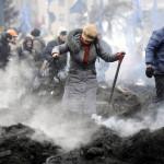 Füstölgő barikádmaradványokat szednek szét kormányellenes tüntetők a Függetlenség terén Kijevben, 2014. február 20-án. MTI Fotó: Beliczay László