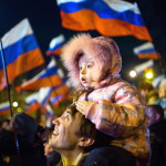 Orosz zászlókkal ünneplő emberek a dél-ukrajnai Krím félsziget hovatartozásáról tartott népszavazás estéjén Szimferopolban 2014. március 16-án. A voksok háromnegyedének megszámlálása után az Ukrajnához tartozó Krími Autonóm Köztársaságban  tartott népszavazás résztvevőinek 95,7 százaléka támogatta, hogy az Ukrajnához tartozó autonóm terület Oroszországhoz csatlakozzon. (MTI/EPA/Hannibal Hannschke)