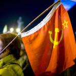 Sarlós-kalapácsos szovjet zászlót fog egy asszony a dél-ukrajnai Krím félsziget hovatartozásáról tartott népszavazás estéjén Szimferopolban 2014. március 16-án. A voksok háromnegyedének megszámlálása után az Ukrajnához tartozó Krími Autonóm Köztársaságban  tartott népszavazás résztvevőinek 95,7 százaléka támogatta, hogy az Ukrajnához tartozó autonóm terület Oroszországhoz csatlakozzon. (MTI/EPA/Hannibal Hannschke)
