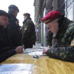 Önkéntes (b) az Ukrán Nemzeti Gárda nevű fegyveres alakulat egyik mobil toborzóközpontjánál a kijevi Függetlenség tere közelében 2014. március 17-én. Az előző napon az Ukrajnához tartozó Krím félszigeten a helyi oroszbarát vezetés által kiírt népszavazáson a lakosok nagy többsége az Oroszországhoz való csatlakozás mellett foglalt állást. (MTI/EPA/Robert Ghement)