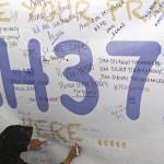 Nő ír a Malaysia Airlines eltűnt MH370-es járatszámú repülőgépének üzenőfalára a Kuala Lumpur-i nemzetközi repülőtéren, Sepangban 2014. március 12-én. A malajziai légitársaság Pekingbe tartó Boeing 777-es gépe kétszáharminckilenc emberrel a fedélzetén márcuis 8-án tűnt el a légiirányítók radarjainak képernyőjéről, feltehetőleg a Dél-kínai-tengerbe zuhant. (MTI/EPA/Ahmad Juszni)/Lai Seng Sin)