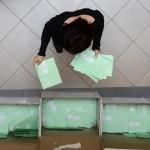 A külképviseleteken leadott szavazatokat tartalmazó urnák felbontása után a voksokat tartalmazó borítékokat válogatják szét Budapesten, a Nemzeti Választási Iroda (NVI) Alkotmány utcai épületében kialakított Nemzeti Választási Központ (NVK) aulájában 2014. április 10-én. Öt asztalnál mintegy negyven irodai munkatárs végzi az urnabontást, és osztja szét a külképviseleteken szavazók voksait tartalmazó zöld borítékokat megyénként külön kartondobozokba. MTI Fotó: Kovács Tamás