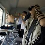 Ortodox zsidók imádkozáshoz készülnek a lengyelországi Oswiecimbe tartó különvonaton 2014. április 28-án, úton a Nemzetközi Élet Menete 27. alkalommal meghirdetett, az egykori auschwitzi koncentrációs táborban tartandó emlékprogramjára. MTI Fotó: Kallos Bea