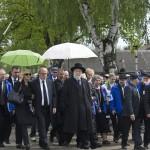 """A Nemzetközi Élet Menete résztvevői áthaladnak az egykori auschwitzi koncentrációs tábor """"Arbeit macht frei"""" felirata alatt  az egykori auschwitzi koncentrációs táborban Oswiecimben 2014. április 28-án. Középen Jiszrael Meir Lau tel-avivi főrabbi holokauszt-túlélő. A megemlékezésen ötvennégy ország képviselőinek részvételével, a magyar zarándokokkal az élen vonult végig a Nemzetközi Élet Menete az auschwitzi egykori haláltáborból a mintegy három kilométerre lévő birkenaui emlékhelyre. MTI Fotó: Kallos Bea"""