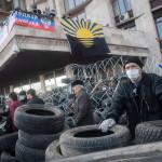 """Oroszbarát tüntetők egy barikád mögött a kelet-ukrajnai Donyeck megye önkormányzatának általuk megszállt épületénél Donyeckben 2014. április 7-én. Az oroszbarát szeparitisták ezen a napon kikiáltották a """"független donyecki köztársaságot"""", amely a döntésük értelmében csatlakozik Oroszországhoz. (MTI/EPA/Roman Pilipey)"""