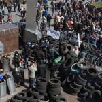 """Oroszbarát tüntetők egy barikád mögött a kelet-ukrajnai Donyeck megye önkormányzatának általuk megszállt épületénél Donyeckben 2014. április 7-én. Az oroszbarát szeparitisták ezen a napon kikiáltották a """"független donyecki köztársaságot"""", amely a döntésük értelmében csatlakozik Oroszországhoz. (MTI/EPA/Photomig)"""