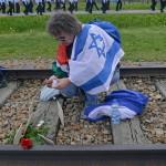 A Nemzetközi Élet Menete felvonulás egyik, magyar és izraeli zászlót vivő magyar résztvevője mécsest gyújt vasúti sínek között az egykori auschwitzi koncentrációs táborból az egykori birkenaui haláltáborba vonulás közben a holokauszt emléknapja alkalmából a lengyelországi Oswiecimben 2014. április 28-án. A menet élén ebben az évben a magyarok mentek a magyar holokauszt 70. évfordulója miatt. (MTI/EPA/Jacek Bednarczyk)