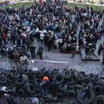 """Oroszbarát tüntetők egy barikád előtt a kelet-ukrajnai Donyeck megye önkormányzatának tüntetők által megszállt épületénél Donyeckben 2014. április 7-én. Az oroszbarát szeparitisták ezen a napon kikiáltották a """"független donyecki köztársaságot"""", amely a döntésük értelmében csatlakozik Oroszországhoz. (MTI/AP/Andrej Baszevics)"""
