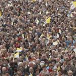 Résztvevők óriáskivetítőn nézik XXIII. János pápának és II. János Pál pápának a Vatikánból közvetített szentté avatási miséjét a krakkói Isteni Irgalmasság bazilikánál 2014. ápriis 27-én. (MTI/AP/Czarek Sokolowski)