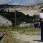 Egy férfi áll az utcán, háttérben az egykori mészkőbánya Tatabánya mésztelepi városrészében 2014. június 20-án. Ezen a napon Czibere Károly, az Emberi Erőforrások Minisztériuma (Emmi) szociális ügyekért és társadalmi felzárkózásért felelős államtitkára látogatást tett az ezerkétszáz lakosú Mésztelepen. MTI Fotó: Kovács Tamás