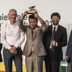 A dél-koreai Min Szuk Cso az Arany Oroszlán-díjjal, amelyet a Crow's Eye View: The Korean Peninsula (A holló szemével: a Koreai-félsziget) című kiállításáért kapott a 14. Velencei Nemzetközi Építészeti Biennálén 2014. június 7-én. Mellette Paolo Baratta, a biennále elnöke (j) és Rem Koolhaas főkurátor (b2). MTI Fotó: Kallos Bea