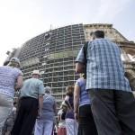 Turisták nézik, amint munkások megkezdik az állványzat eltávolítását a Colosseum egyik oldaláról Rómában 2014. július 7-én, miután befejeződött az amfiteátrum felújításának első szakasza. A 25 millió eurós (mintegy 7 milliárd forintos) felújítást a Tod's olasz cipőgyártó cég fizeti. (MTI/EPA/Massimo Percossi)