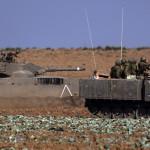 Izraeli katonák harcjárműve és egy Merkava tank Izrael és a Gázai övezet határán 2014. július 10-én. Az izraeli hadsereg július 8-án hadműveletet indított a Gázai övezet ellen a palesztin fegyveresek Izrael elleni rakétatámadásainak leállítására. A három napja tartó légi offenzívában eddig legkevesebb 57 palesztin vesztett életét, köztük  legalább hét nő és 14 gyerek. (MTI/EPA/Atef Szafadi)