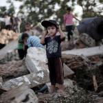 Palesztin kisfiú áll az izraeli rakéták becsapódása következtében megsemmisült házuk romjai között a ciszjordániai Bét-Hanun városában 2014. július 9-én. Az izraeli hadsereg július 8-án hadműveletet indított a Gázai övezet ellen a palesztin fegyveresek Izrael elleni rakétatámadásainak leállítására. A három napja tartó légi offenzívában eddig legkevesebb 57 palesztin vesztett életét, köztük  legalább hét nő és 14 gyerek.  (MTI/AP/Halil Hamra)