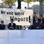 """A Német Almák Frontja (Front Deutscher Äpfel) szatirikus szervezet tagjai a jelenlegi magyar politikai helyzet ellen tiltakoznak és """"Valódi magyarok vagyunk!"""" jelentésű, gót betűs feliratú transzparenset mutatnak fel Lipcsében 2014. október 9-én. A városban tartózkodik Áder János köztársasági elnök és részt vesz az egykori NDK-ban, azaz Kelet-Németországban lezajlott békés forradalom 25. évfordulója alkalmából rendezett ünnepségeken. (MTI/EPA/Jan Woitas)"""