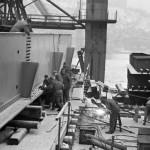 1964. január 7. A Ganz-MÁVAG Daru- és Hídgyár munkásai az újjászülető Erzsébet híd vasszerkezetén dolgoznak, a szegecsfejeket alakítják ki a kemény hidegben. Előtérben egy munkás lánghegesztővel fémet vág, a háttérben a havas Gellért-hegy. MTI Fotó: Bodnár László