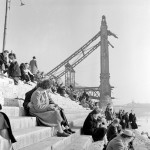 1959. március 1. Budapestiek ülnek a Duna-part lépcsőjén. A háttérben az Erzsébet híd romjai. MTI Fotó: Lajos György