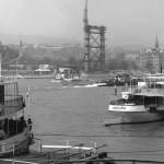 1963. április 18. A Csehszlovák Utazási Iroda béreli a Dunaj nevű szovjet hajót, amelyen hetenként több száz turista érkezik Budapestre. Nemzetközi kapcsolatainkat a Duna és a rajta vonuló hajóforgalom is jelzi. A tengert és a nyugati országokat összekötő nagy vízi út egyik gócpontja a csepeli Nemzeti és Szabadkikötő. Itt rakják át a tengerről érkező és továbbhaladó árukat. A személyforgalom is örvendetesen nő.  A hajók mögött az újjáépülő Erzsébet híd budai pillére látható építés közben. MTI Fotó: Lajos György
