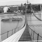 1963. szeptember 6. Az Erzsébet híd pilonjai között már feszülnek az első, élénkpirosra festett kábelek. A Ganz-MÁVAG hídépítői jó ütemben, naponta átlag egy kábelt húznak át. Így – ha az idő megengedi – november elejéig befejezik a kétszer 61 kábel áthúzását. Szemben, a pesti oldalon a Március 15. tér a Belvárosi Templommal és az ELTE (Eötvös Loránd Tudományegyetem) Bölcsészkarának épülete. MTI Fotó: Lajos György