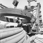 1963. szeptember 6. A budai hídfőn újabb kábeltekercset helyeznek a forgódobra, amelyről az áthúzás történik. Az Erzsébet híd pilonjai között már feszülnek az első élénkpiros kábelek. A Ganz-MÁVAG hídépítői jó ütemben, naponta átlag egy kábelt húznak át a budai partról a pesti oldalra. A kifeszített kábeleket rögtön átfestik, egy-két napig pihentetik, majd pontosan a többi mellé illesztik. A kábelköteg gyorsan vastagodik, ha az idő megengedi, november elejéig befejezik a kétszer 61 kábel áthúzását. MTI Fotó: Lajos György
