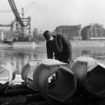 1964. február 14. Egy építőipari munkás a hídelemeket vizsgálja az épülő Erzsébet híd budai hídfőjénél. A háttérben zajlik a jég a Dunán. MTI Fotó: Lajos György