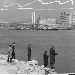 1965. március 14. Horgászok a budai Duna-parton, a nemrégiben újjáépített Erzsébet-híd közelében, tavaszi napsütésben. A híd előterében, a Duna másik partján balról jobbra: az V. kerület Belgrád rakpart 27. eklektikus és a 26. számú szecessziós épülete látszódik az Irányi utca torkolatában. MTI Fotó: Lajos György