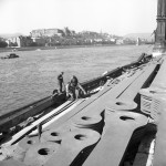 1957. október 11. A munkások szétszedik az Erzsébet híd vízből kiszedett utolsó láncsorának láncszemeit a Duna pesti rakpartján a híd helyreállításának munkálataikor. MTI Fotó: Fényes Tamás