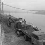 1964. március 25. A rakpart korlátjának támaszkodva figyeli egy fiatalember a budai rakparton dolgozó markolót, háttérben az épülő Erzsébet híd. MTI Fotó: Bojár Sándor
