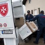 A szállítmányozó cég munkatársai visznek egy háztartási gépet a szerbiai Obrenovacban 2014. december 10-én. Kályhát, mosógépet, hűtőszekrényt, tűzhelyet kapott 105 szerb család a Magyar Máltai Szeretetszolgálattól a Belgrádhoz közeli településen, amelyet a legsúlyosabban érintettek a májusi pusztító árvizek. MTI Fotó: Marjai János