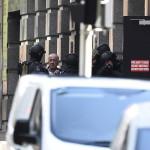 Rohamrendőrök és egy szabadon engedett túsz (b2) annak a sydneyi kávéháznak a közelében 2014. december 15-én, ahol iszlamisták túszul ejtettek több embert. A rendőrség legalább egy fegyveres túszejtőről beszélt, azt viszont továbbra sem közölte, hogy hány embert tartanak fogva. (MTI/EPA/Dan Himbrechts)