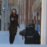 Egy szabadon engedett túsz szalad egy rohamrendőr felé annak a sydneyi kávéháznak a közelében 2014. december 15-én, ahol iszlamisták túszul ejtettek több embert. A rendőrség legalább egy fegyveres túszejtőről beszélt, azt viszont továbbra sem közölte, hogy hány embert tartanak fogva. (MTI/AP/Rob Griffith)