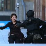 Egy szabadon engedett túsz szalad rohamrendőrök felé annak a sydneyi kávéháznak a közelében 2014. december 15-én, ahol iszlamisták túszul ejtettek több embert. A rendőrség legalább egy fegyveres túszejtőről beszélt, azt viszont továbbra sem közölte, hogy hány embert tartanak fogva. (MTI/AP/Rob Griffith)