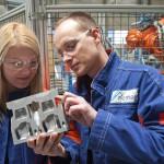 Kampós Katalin és Szüllő András munkatársak egy alumínium mintadarabot ellenőriznek a Nemak Győr Kft. győri üzemében 2015. január 27-én. A kormány stratégiai megállapodást kötött ezen a napon a kft.-vel, amely a Nemak vállalatcsoport legnagyobb európai hengerfejgyártó üzeme. A mexikói székhelyű Nemak cégcsoport csúcstechnológiájú alumínium hengerfejeket gyárt a világ vezető autóipari vállalatai számára. MTI Fotó: Krizsán Csaba