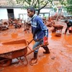 Devecser, 2010. október 6. Helybeliek talicskán hordják ki kertjükből a vörösiszapot Devecseren, miután a Magyar Alumínium Termelő és Kereskedelmi Zrt. (MAL Zrt.) Ajka melletti tározójából 2010. október 4-én mintegy egymillió köbméternyi mérgező, maró hatású vörösiszap ömlött ki gátszakadás miatt. A katasztrófa három települést - Devecser, Kolontár, Somlóvásárhely – érint, közel 40 négyzetkilométeres terület lakossága és élővilága van veszélyben. MTI Fotó: Kovács Tamás
