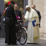 Ferenc pápa (j) megádlja a családról szóló rendes püspöki szinódus ülésén résztvevő egyik főpap kerékpárját a Vatikánban 2015. október 14-én. A közel 300 bíboros, püspök és prelátus részvételével zajló pápai tanácskozás október 24-én ér véget. (MTI/Andrew Medichini)