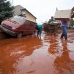 Emberek értékeiket viszik egy fennakadt mikrobusz mellett Devecseren, miután a Magyar Alumínium Termelő és Kereskedelmi Zrt. (MAL Zrt.) Ajka melletti tározójából 2010. október 4-én mintegy egymillió köbméternyi mérgező, maró hatású vörösiszap ömlött ki gátszakadás miatt. A térségben katasztrófahelyzet alakult ki. Az áradás három települést - Devecser, Kolontár, Somlóvásárhely - öntött el. Mintegy 40 négyzetkilométeres terület lakossága és élővilága van veszélyben. MTI Fotó: Mohai Balázs