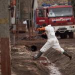 Egy önkéntes átugrik egy árkon, amelyben vörösiszap van, az ipari katasztrófa által sújtott Devecseren. MTI Fotó: Mohai Balázs
