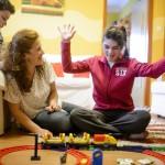 A háromgyermekes édesanya, Szalainé Forgács Klaudia (k) az autisztikus tünetekkel élő Lilivel játszik otthonukban, Karancskesziben 2016. március 3-án. Férjével mindhárom gyermekük születését tervezték és átgondolták, főleg a 17 éves nagylányuk, az autista és epilepsziás Lili miatt. A pár szerint egy gyermek születése komoly próbatétel, különösen akkor, ha valamiért eltér az átlagtól, és ha a házastársak egymást erősítik, akkor megvalósíthatják álmaikat, elérhetik céljaikat és semmiről sem kell lemondaniuk.<br /> MTI Fotó: Komka Péter