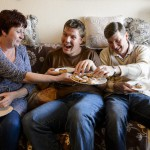 """Tóthné Bus Krisztina (b) a 27 éves autista fiával, Balázzsal (k) és férjével, Gáborral budapesti lakásukban 2016. március 9-én. A pedagógusnő saját elmondása szerint """"ajándékba kapott"""" két félárva gyermeket házassága révén, egyikük autista. Balázst szülei megtanították egyedül közlekedni, fürdeni és öltözni. A fiatal férfi jelenleg külön lakásban él, konyhai kisegítőként dolgozik. 2015-ben a paraevezős világbajnokságon arany- és bronzérmet szerzett.<br /> MTI Fotó: Komka Péter"""