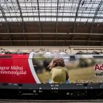 """A Magyar Máltai Szeretetszolgálat társadalmi üzeneteit megjelenítő mozdonya a budapesti Keleti pályaudvaron, ahonnan útjára indították 2016. május 10-én. A felmatricázott, Traxx típusú mozdony egyik oldalán egy kislány és az """"Adjunk esélyt nekik!"""" felirat, a másikon a Máltai Mentőszolgálat mentőautója és a """"Segítségére sietünk"""" szöveg látható. A mozdony belföldi vonatokat húz majd és a tervek szerint két éven át hívja fel a figyelmet azokra, akik segítségre szorulnak.<br /> MTI Fotó: Balogh Zoltán"""