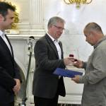Dobos Menyhért, a Duna Médiaszolgáltató vezérigazgatója (k) és Vaszily Miklós, a Médiaszolgáltatás-támogató és Vagyonkezelő Alap (MTVA) megbízott vezérigazgatója (b) átadja a Karinthy-gyűrűt Szőke András humoristának a Magyar Rádió Márványtermében 2016. június 29-én.<br /> MTI Fotó: Máthé Zoltán