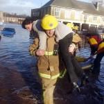 Tűzoltók mentik ki a helybelieket a vízzel elöntött házukból az angliai Carlislében 2005. január 8-án, amikor az utóbbi évek legpusztítóbb, özönvízszerű esőzéssel kísért orkánja pusztított Nagy-Britanniában. Az ítéletidő főleg Skóciát és Anglia északnyugati vidékeit, valamint Walest sújtotta (MTI/EPA/John Giles)
