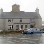 Az utcákon hömpölygő vízben áll egy autó a skóciai Orkney szigetén fekvő Ronaldsay faluban (MTI/EPA/Frank Bradford)