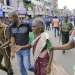 Idős asszonynak segítenek távozni a Szent Antal tempomból (Fotó: MTI/AP/Eranga Jayawardena)