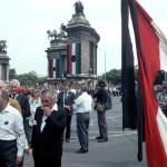 """Budapest, 1989. június 16.<br /> A gyásznapon, június 16-án Nagy Imrére és sorstársaira emlékeztek a Hősök terén, ahol a felállított ravatalnál az ország népe leróhatta tiszteletét, elhelyezve a kegyelet virágait a mártírok koporsói előtt. Ezután a Rákoskeresztúri Újköztemető 301-es parcellájában helyezték örök nyugalomra az elhúnytakat.<br /> A képen: a híres """"lyukas zászló"""" a Hősök terén (Fotó: MTI/Kisbenedek Attila)"""